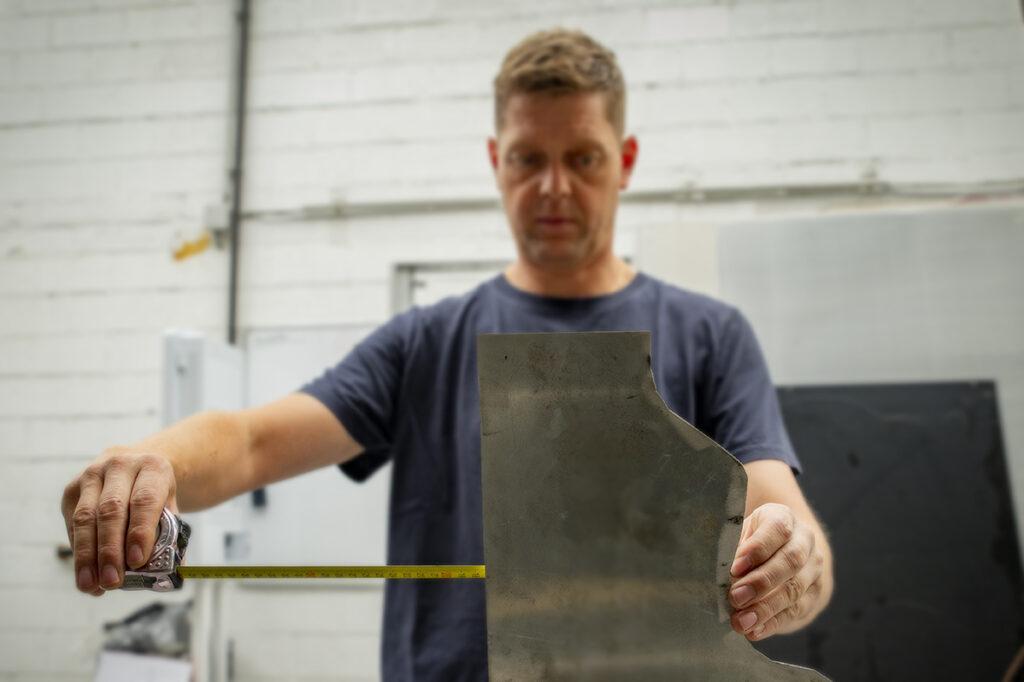 een stuk metaal wordt afgemeten met een rolmeter om nadien af te knippen op de knipbank. Dit stuk wordt gebruikt om een lasconstructie voor een metalen kast gecombineerd met hout te maken.