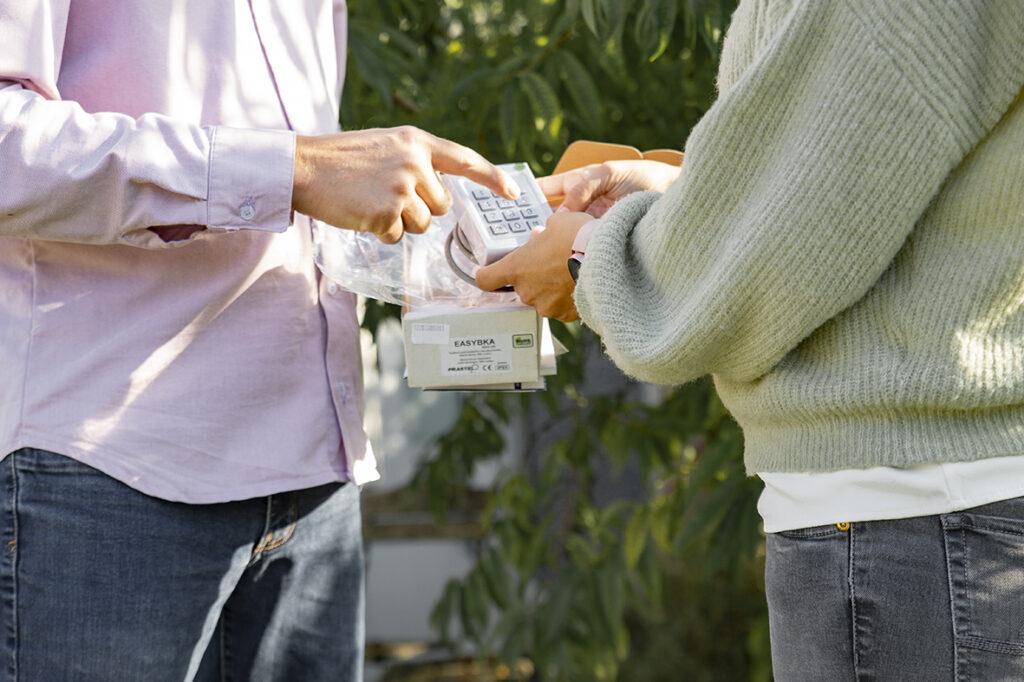 De zaakvoerder toont een toetsenklavier voor het openen van een geautomatiseerde poort. De klant houdt het toetsenklavier vast. De zaakvoerder geeft uitleg over het gebruik van de automatisatie.